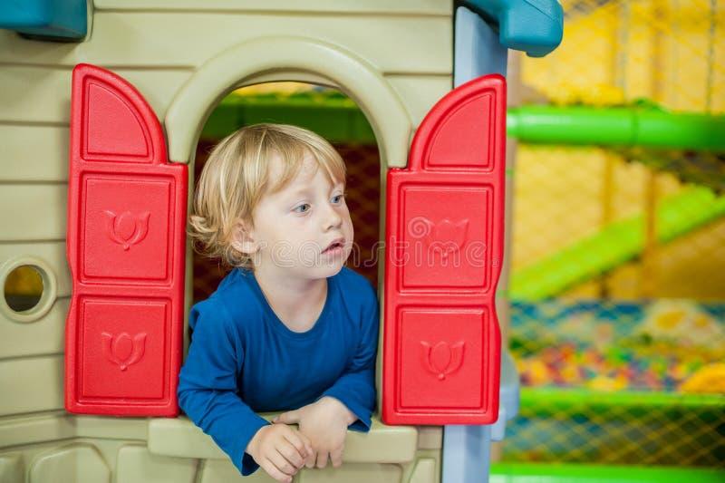 小孩男孩看在房子外面 免版税库存照片