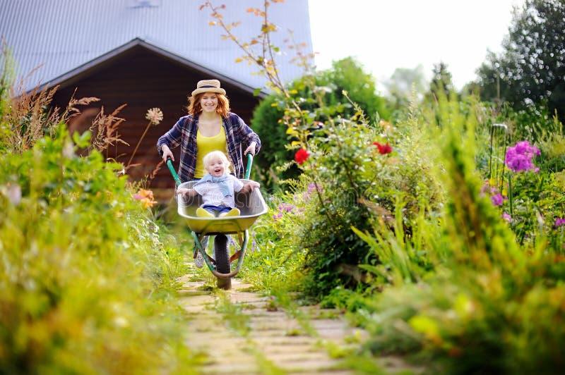 小孩男孩获得乐趣在推挤由妈咪的独轮车在国内庭院里 图库摄影