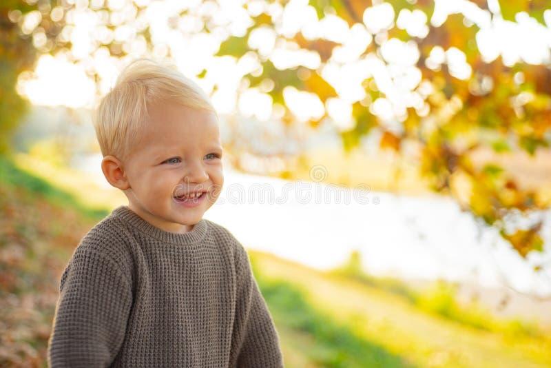 小孩男孩蓝眼睛享受秋天 小小小孩在晴朗的秋天天 温暖和舒适 E ? 图库摄影
