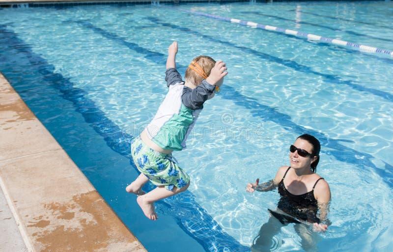 小孩男孩跳进与等待的母亲的水池捉住他 免版税图库摄影