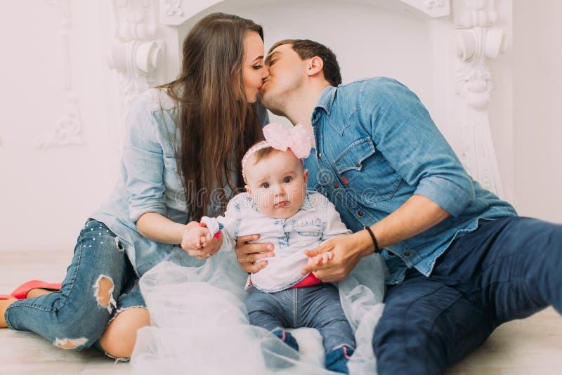 小孩的特写镜头画象坐地板在亲吻的背景做父母 免版税库存照片