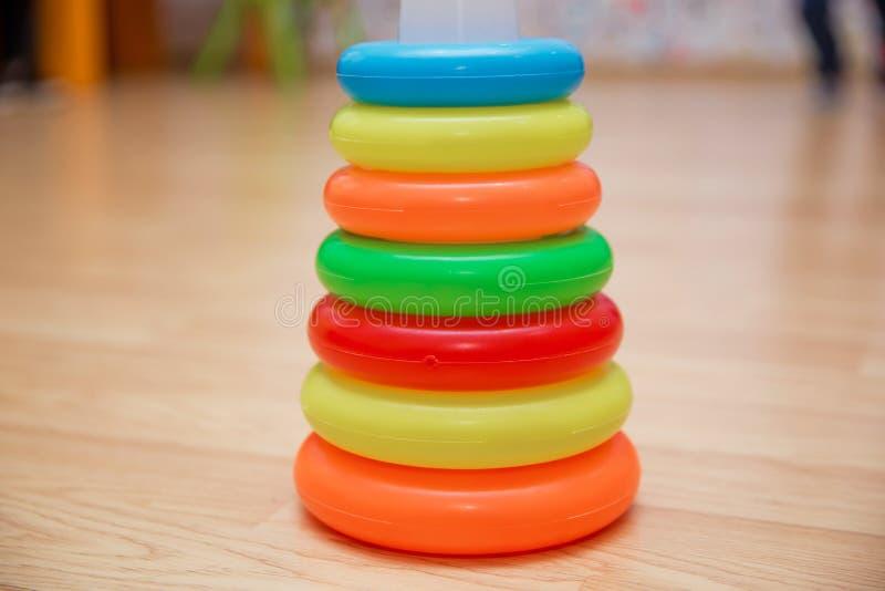 小孩的,压环教育玩具,隔绝在黄色 被堆积的圆块五颜六色的金字塔  金字塔修造为 库存图片