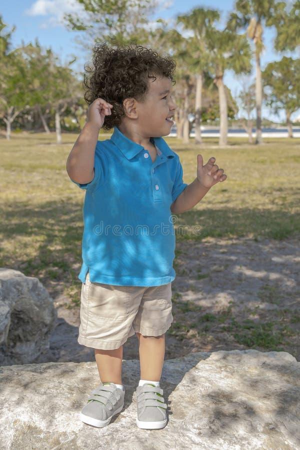 小孩站立在一个大岩石在公园,朝他的左边看 图库摄影