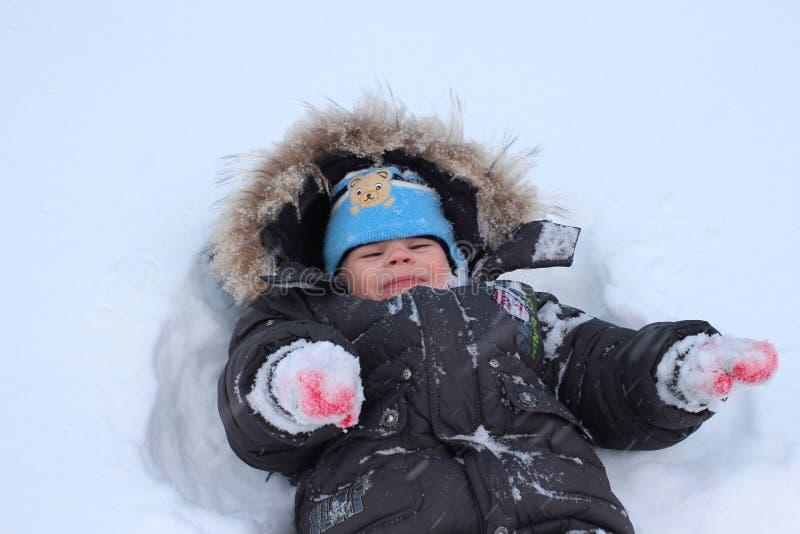 小孩笑的冬天在获得的雪下跌乐趣 免版税库存图片