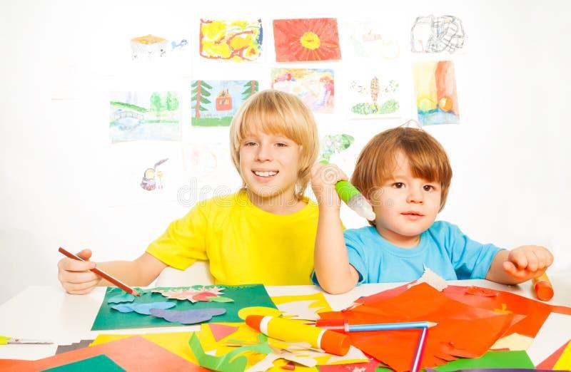 小孩繁忙与纸和胶浆 免版税库存图片