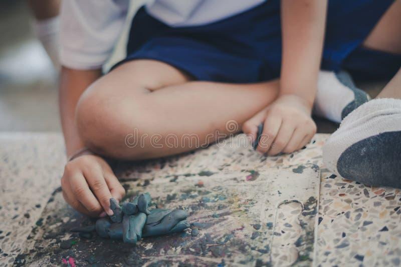 小孩获得乐趣与在Th的五颜六色的雕塑黏土一起 免版税库存照片