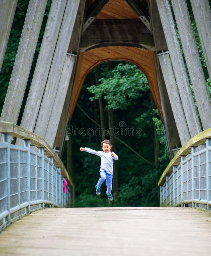 小孩获得乐趣通过跑和跳跃 免版税库存照片