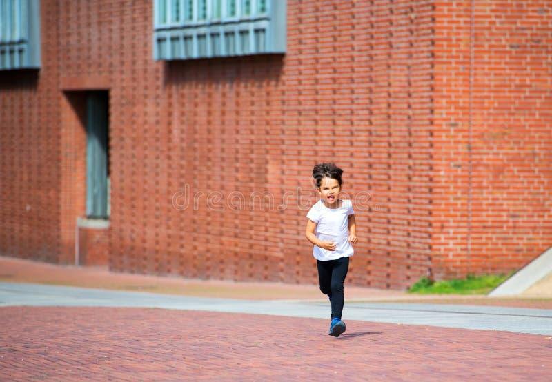 小孩获得乐趣通过跑在街道上 库存图片