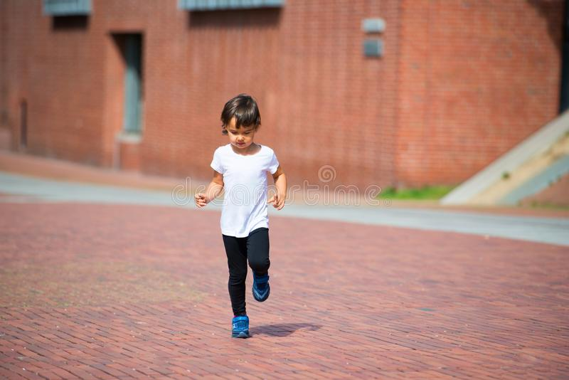 小孩获得乐趣通过跑在街道上 库存照片