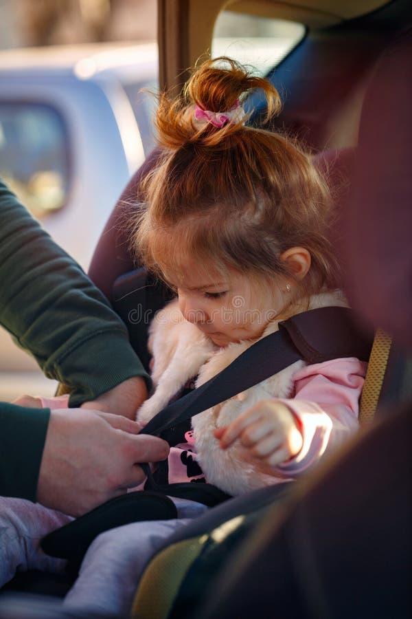 小孩逗人喜爱的女孩折了入她的汽车座位 免版税库存图片