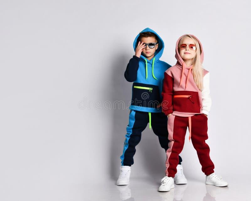 小孩,男孩和女孩,戴着墨镜和头罩,彩色运动服,运动鞋 他们在白色工作室背景中独立摆姿势 库存图片