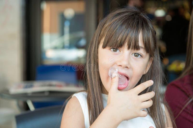 小小女孩舔他的手指 免版税图库摄影