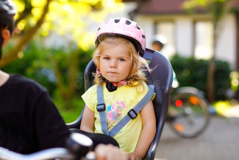 小小孩女孩画象有安全盔甲的在坐在父母自行车位子的头  自行车的男孩 免版税库存照片