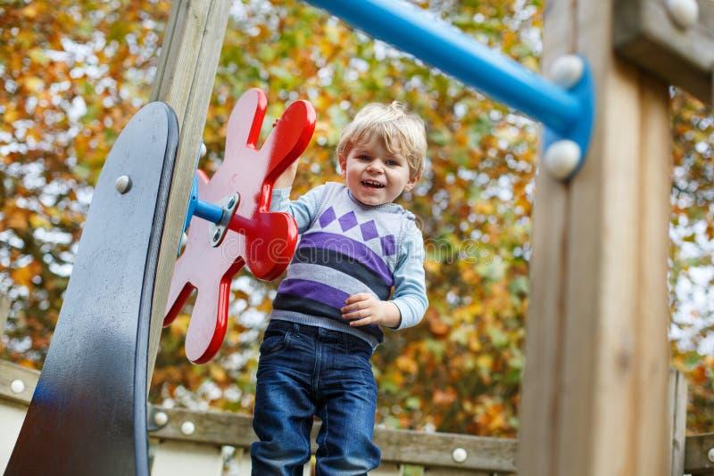 小小孩男孩获得在操场的乐趣在秋天 免版税图库摄影