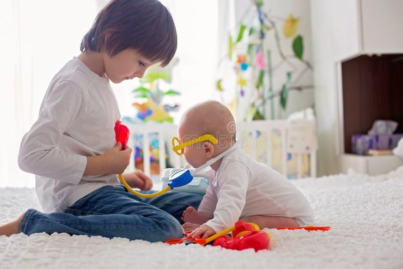小小孩男孩,在家使用与他的弟弟 免版税库存照片