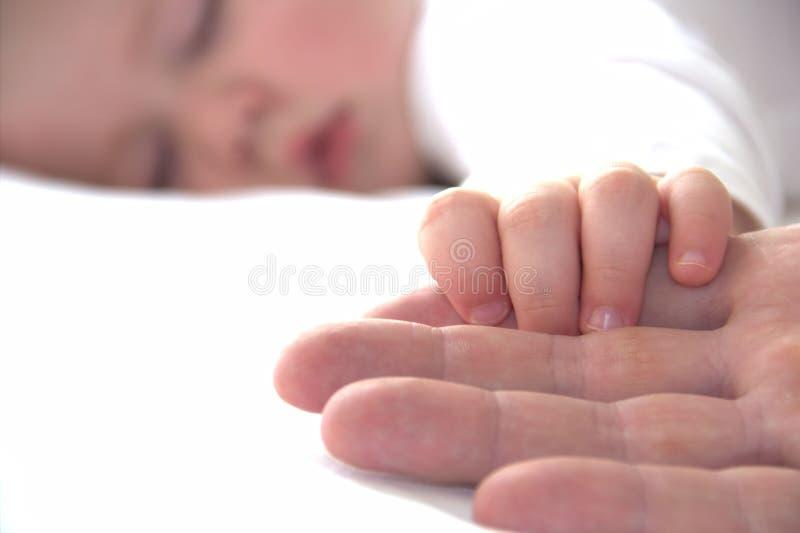 小小睡的男孩握爸爸的手 免版税库存照片