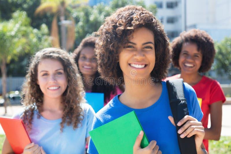 小小组笑非洲白种人和拉丁女学生 图库摄影