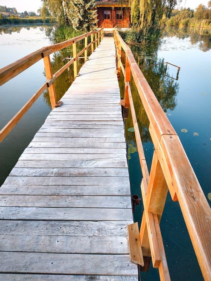 小屋一海岛 与桥梁的风景对湖的房子 库存照片