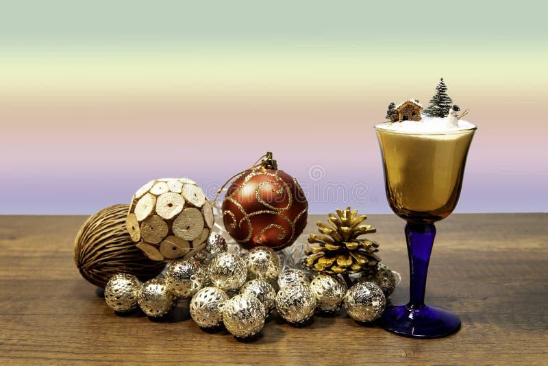 小屋和雪人在杯酒与圣诞节球装饰 免版税库存照片