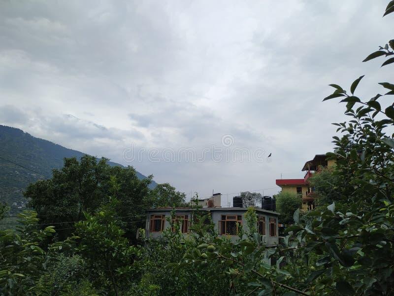 小山、多云天气和美丽的小村庄的房子 免版税库存照片