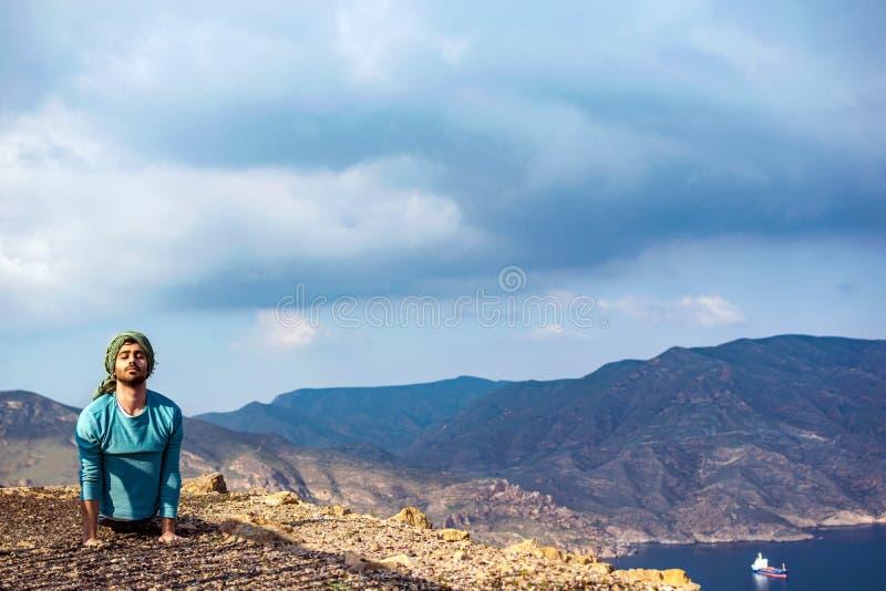 小山上缘执行瑜伽的峭壁岩石的年轻印度人 免版税库存图片