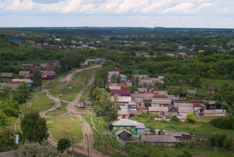从小山到村庄和街道的弯曲道路的看法 图库摄影