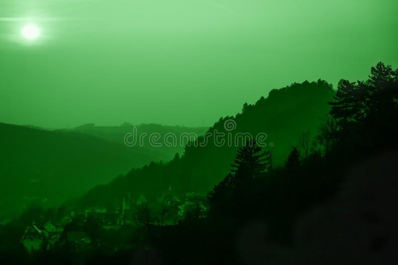 小山和老镇全景  被定调子的绿色薄菏 E 免版税库存照片