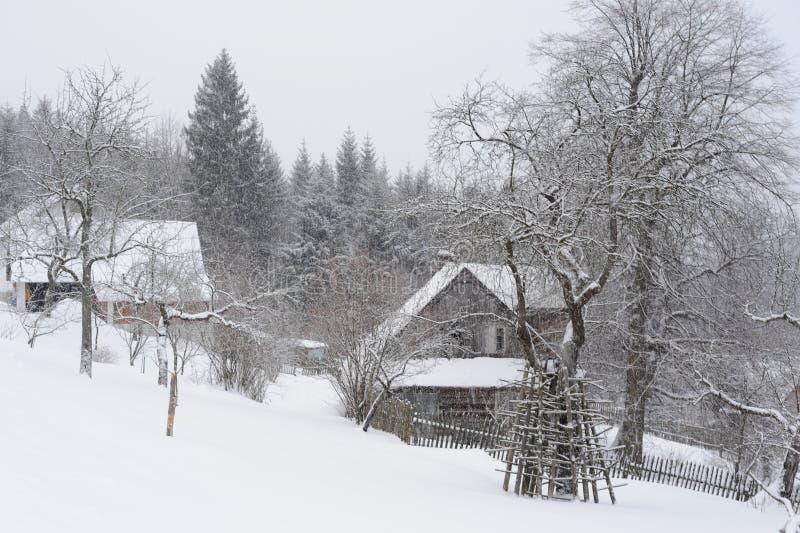 小山的一个偏僻的老木房子在暴风雪期间在波兰的南部的冬天 库存照片