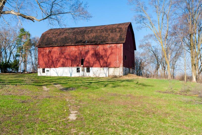 小山的一个被风化的红色谷仓 免版税图库摄影