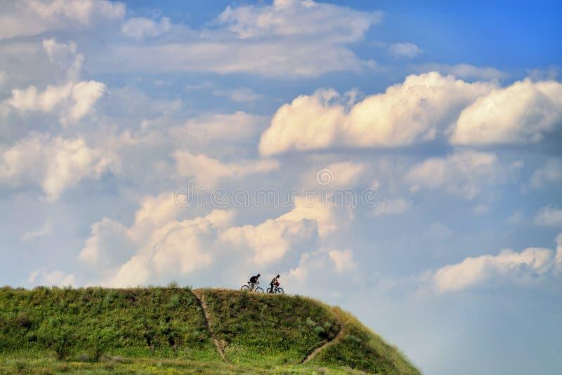 小山的两个山骑自行车的人在Khodosivka, Kyiv,乌克兰, 25 免版税库存照片