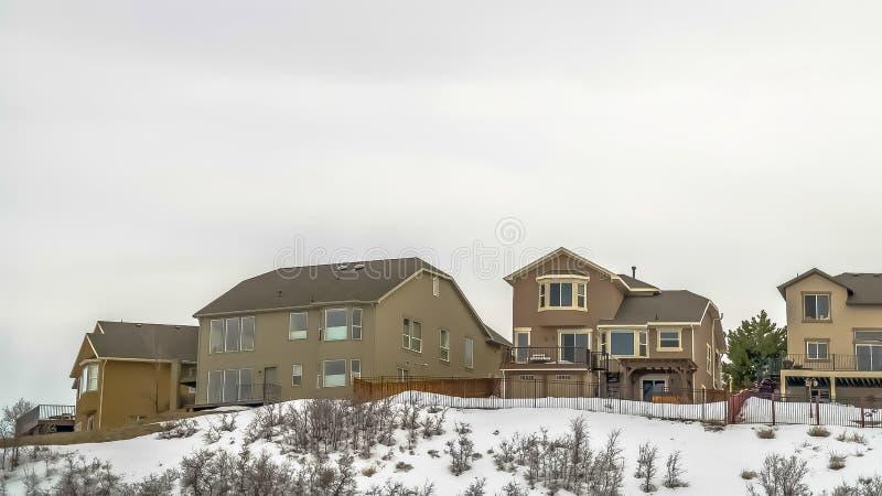 小山的全景框架多楼层房子在浩大的阴暗天空下在一寒冷冬天天 免版税库存图片