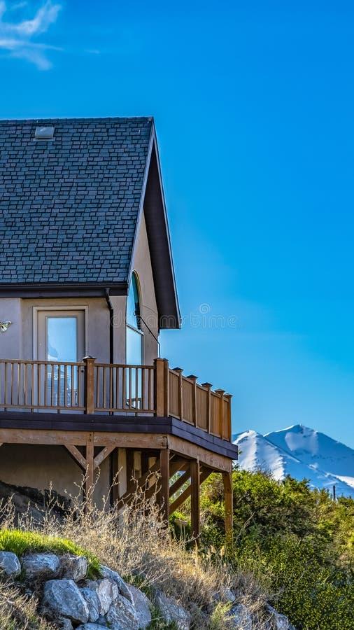 小山的垂直的议院与俯视多雪的山和明亮的天空蔚蓝的阳台 免版税库存图片