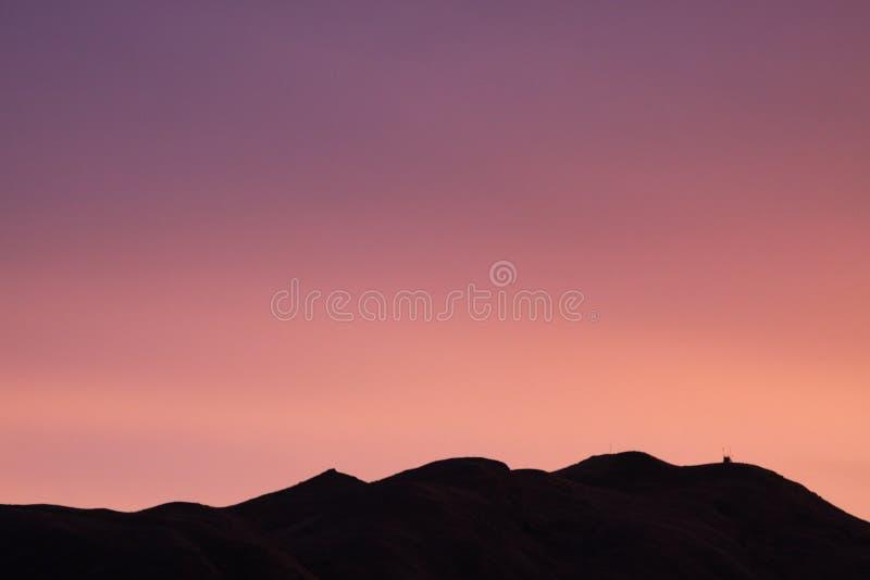 小山的现出轮廓的范围反对桃红色日落天空的 免版税库存图片