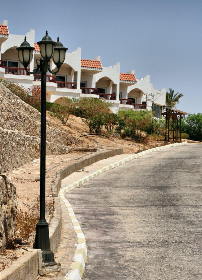 小山的路在房子和街灯附近 库存照片