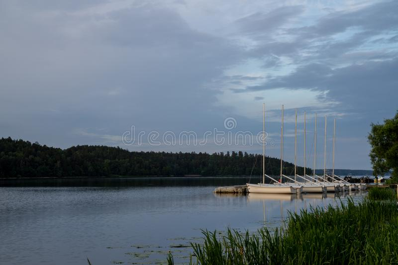 小帆船位置行在瑞典停泊了,并行,在湖Malaren一个平静的海湾,一个夏天早晨 库存照片