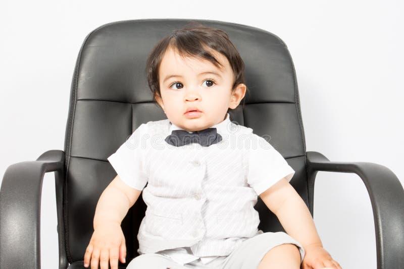 小幼儿男孩看起来的椅子隔绝坐白色背景 库存图片