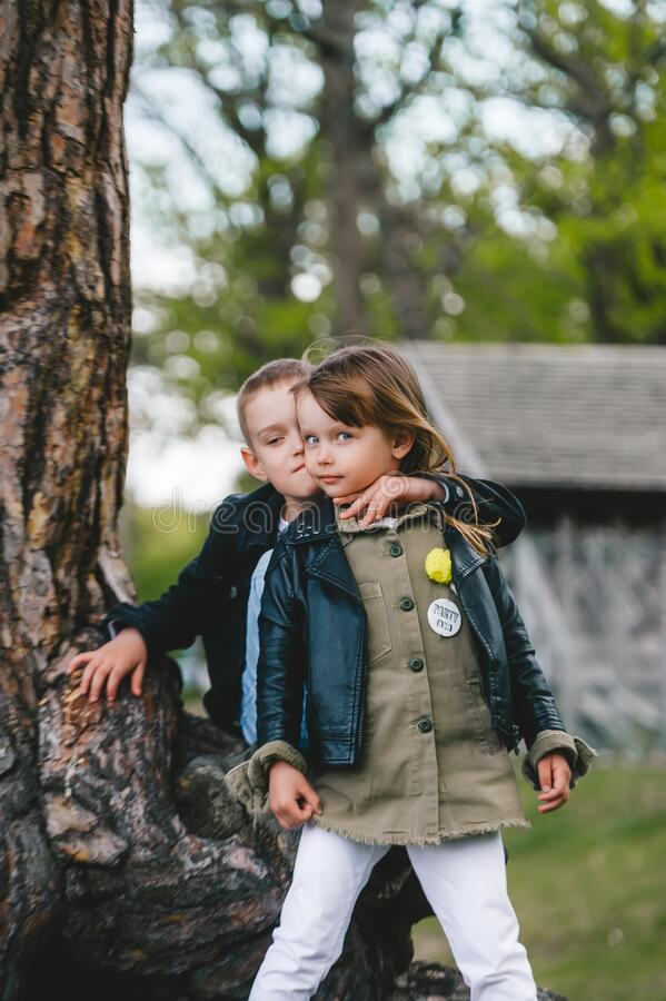 小弟妹站在树干旁拥抱 免版税库存图片