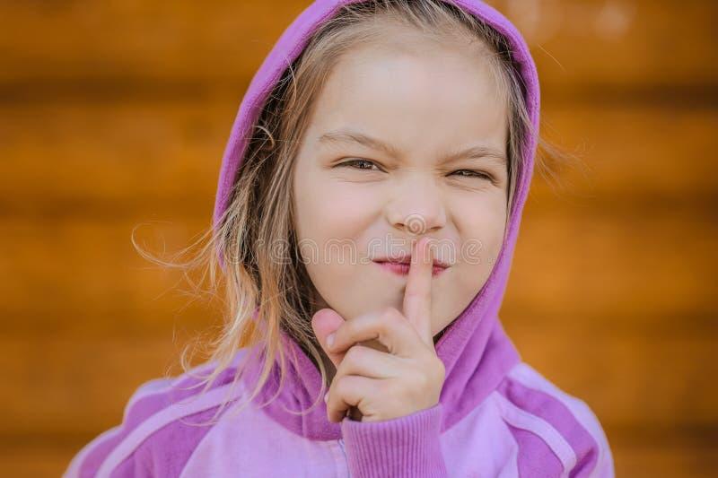 小微笑的女孩投入食指到嘴唇 免版税库存图片