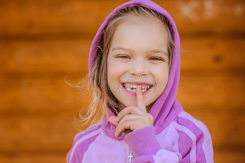 小微笑的女孩投入食指到嘴唇 免版税库存照片