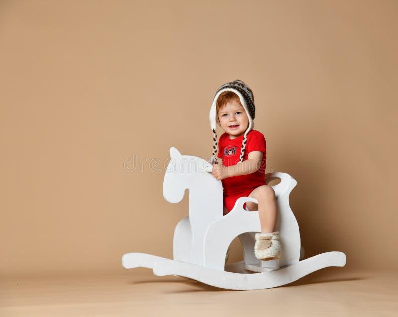 小微笑的婴孩坐一个白马,木晃动 免版税库存照片