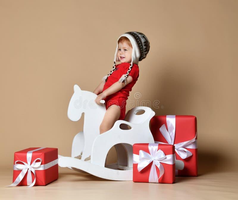 小微笑的婴孩坐一个白马,木晃动 图库摄影