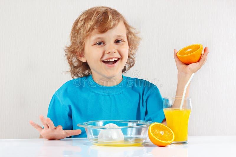 小微笑的男孩由桔子做汁液 库存图片