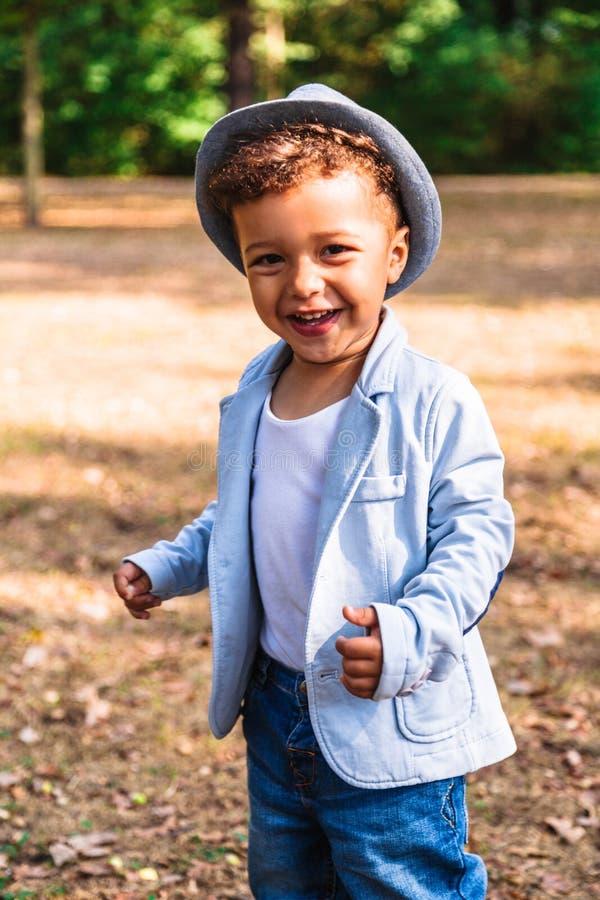 小微笑的男孩画象在帽子和夹克户外 免版税库存图片