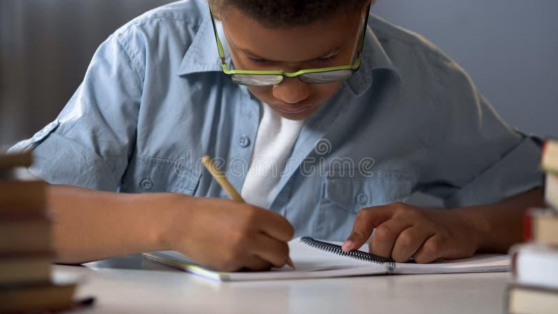 小心地写信的一年级学生男孩在他的习字簿,做家庭作业 免版税图库摄影
