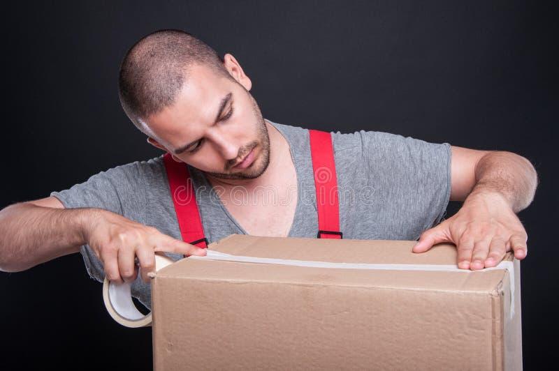 小心地包装有胶带的搬家工人人箱子 免版税库存照片