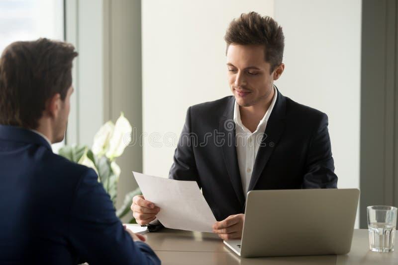 小心地读合同期限的企业家 库存照片
