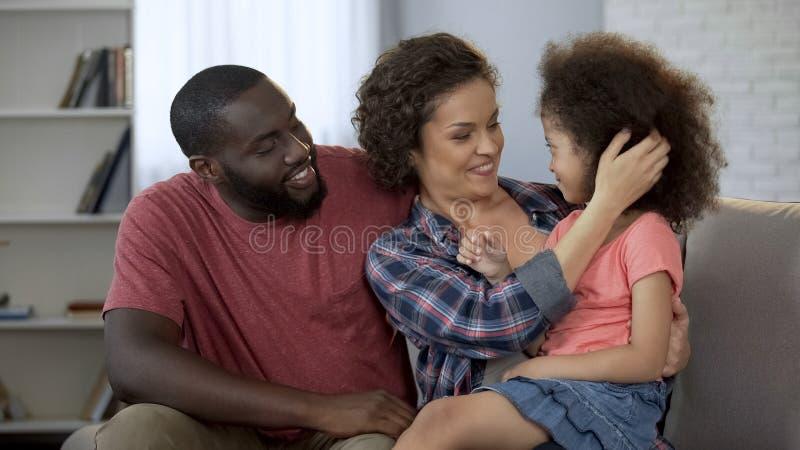 小心地调整她的小女儿、父母亲温暖和爱的头发的妈妈 免版税库存照片