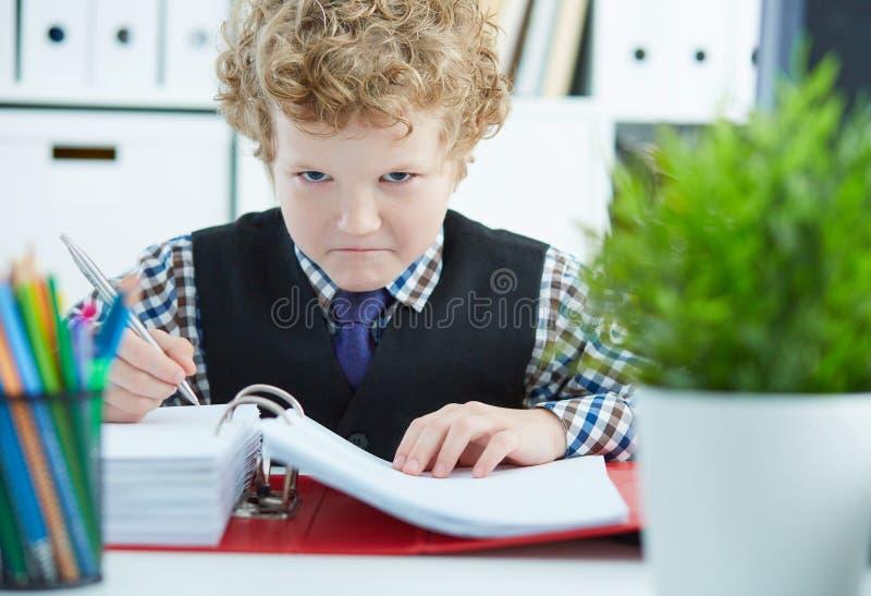 小恼怒的卷曲白种人男孩在办公室喜欢做文书工作的商人 免版税库存图片