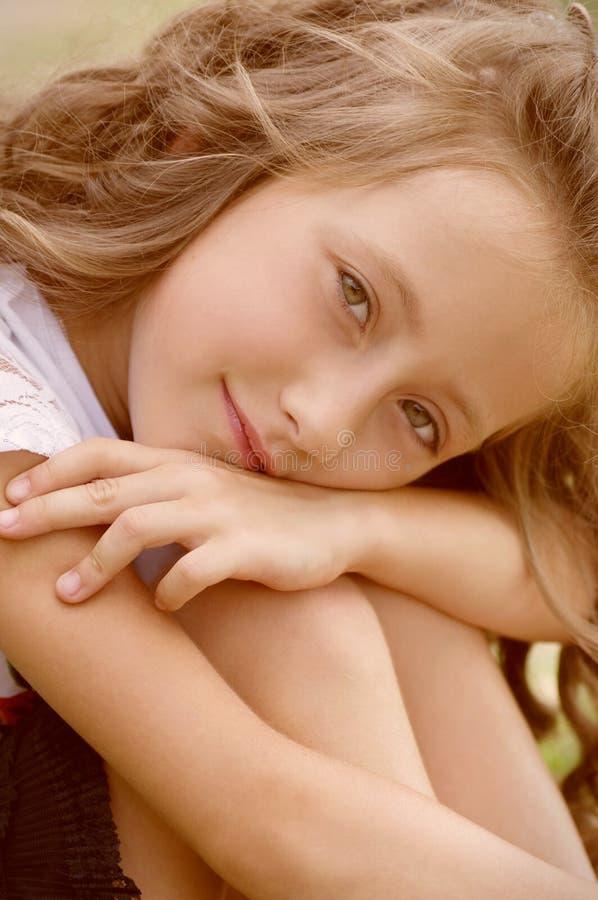 小愉快的女孩在庭院里 免版税库存照片