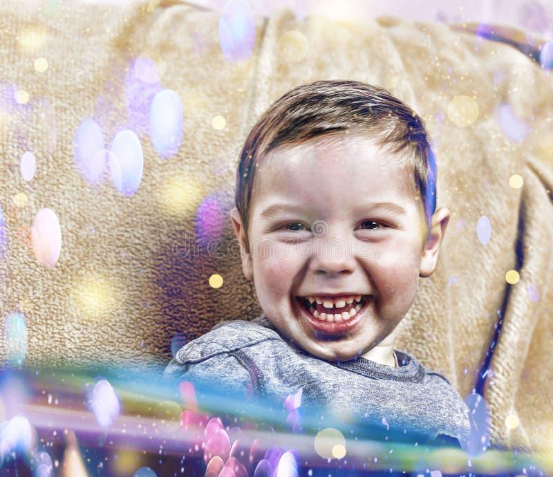 小愉快的男孩笑,当在家坐沙发在圣诞节内部时 免版税库存图片